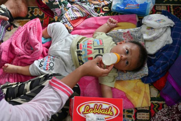 Un bébé boit du lait dans un centre pour personnes déplacées à Carita, dans la province de Banten, le 24 décembre 2018 en Indonésie [ADEK BERRY / AFP]