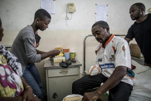 Beckley Motome reçoit l'aide de sa famille pour manger sur son lit d'hôpital de Buea, le 4 octobre 2018 [MARCO LONGARI / AFP]