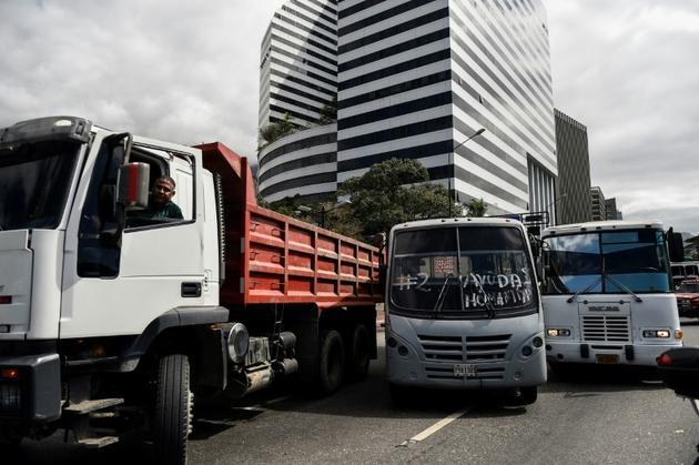 Camions et autocars utilisés pour prendre livraison de l'aide humanitaire envoyée par les Etats-Unis et le Brésil, lors d'un rassemblement en soutien à l'opposant vénézuélien Juan Guaido, le 20 février 2019 à Caracas [Federico Parra                       / AFP]