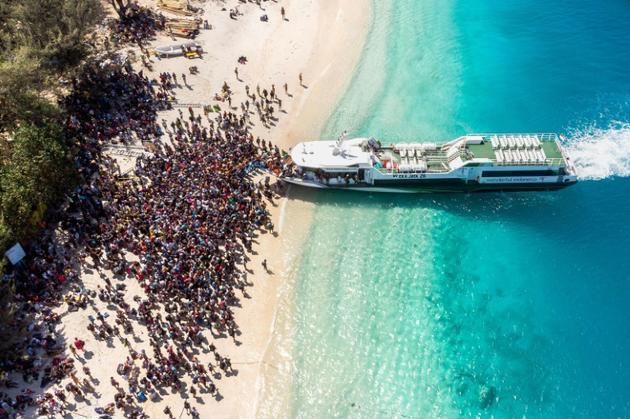 Vue aérienne d'une foule attendant de quitter l'île indonésienne de Gili Trawangan, voisine de celle de Lombok, frappée dimanche par un séisme meurtrier, le 8 août 2018 [Melissa DELPORT / @trufflejournal/AFP]
