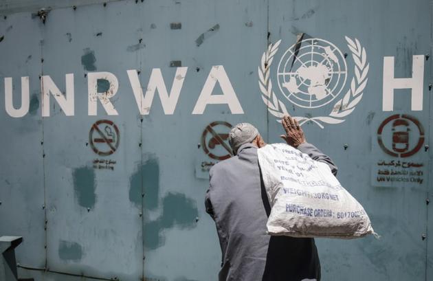 Un Palestinien devant l'emblème de l'Unrwa, l'agence de l'ONU pour les réfugiés palestiniens, devant ses bureaux de la ville de Gaza, le 31 juillet 2018 [SAID KHATIB / AFP]