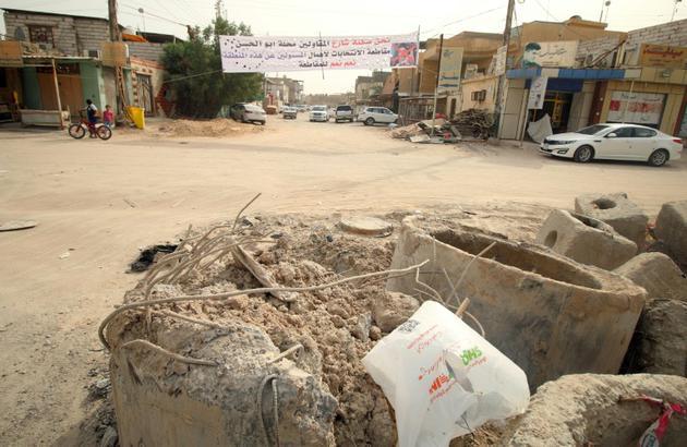 Une bannière appelle les Irakiens à boycotter les élections législatives dans un quartier de Bassora (sud) le 8 mai 2018 alors que les habitants de cette région se plaignent d'être négligés par les autorités fédérales [HAIDAR MOHAMMED ALI / AFP]