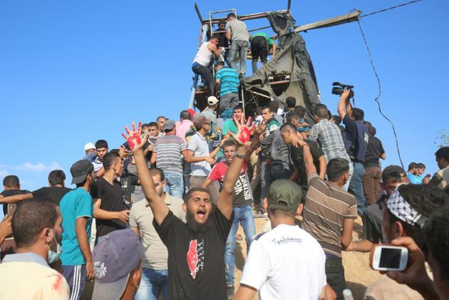 Des Palestiniens protestent après la destruction d'un poste d'observation du Hamas près de Khan Younis le 20 juillet 2018 [SAID KHATIB / AFP]