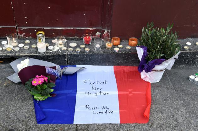 """Des bougies, des fleurs et un drapeau français flanqué de la devise de Paris """"Fluctuat nec Mergitur"""" sont déposé près du bar Le Carillon, le 14 novembre 2015 [DOMINIQUE FAGET / AFP]"""