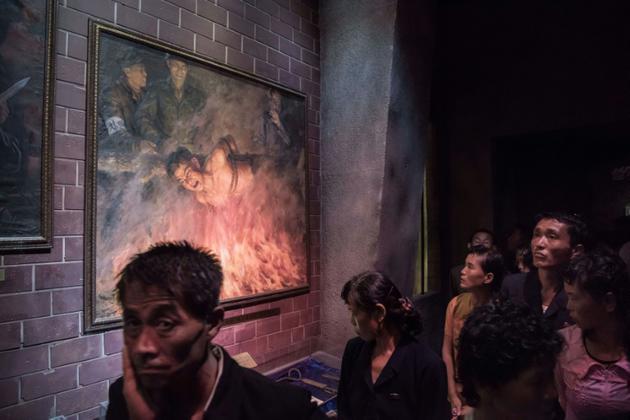 Un groupe de visiteurs passe devant un tableau représentant des soldats américains brûlant un Nord-Coréen, le 24 juillet 2017 au Musée des atrocités de guerre américaines à Sinchon, en Corée du Nord [Ed JONES / AFP]