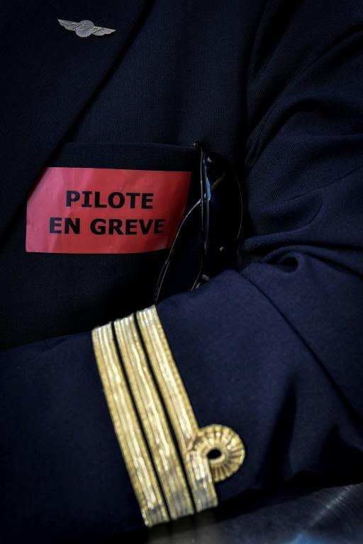 """Un pilote d'Air France portant une insigne """"en grève"""", le 24 avril 2018 à l'aéroport Roissy-Charles de Gaulle [STEPHANE DE SAKUTIN / AFP/Archives]"""