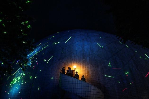 Des manifestants pointent les faisceaux de leurs pointeurs laser sur le dôme du Musée de l'Espace, le 7 août 2019 à Hong Kong [Philip FONG / AFP]