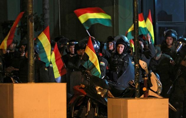 Des policiers boliviens brandissent le drapeau national après avoir rejoint le mouvement de mutinerie à Santa Cruz, Bolivie, le 6 novembre 2019 [DANIEL WALKER / AFP]