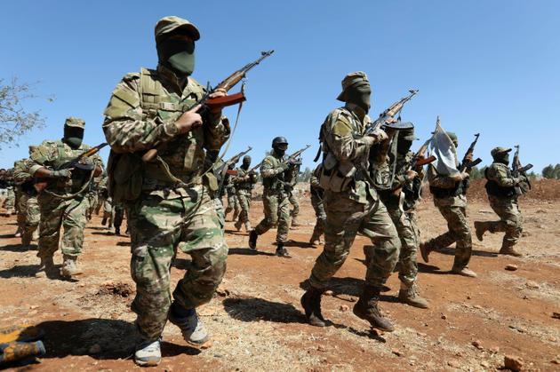 Des combattants syriens participent à des exercices militaires dans un camp d'entraînement du groupe jihadiste Hayat Tahrir al-Cham dans une région de la province syrienne d'Idleb, menacée d'une offensive du régime, le 14 août 2017 [OMAR HAJ KADOUR / AFP]