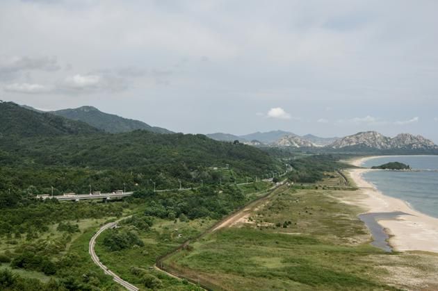 Un convoi d'autocars transportant les participants d'une réunion familiale intercoréenne traverse la zone démilitarisée DMZ en direction de la Corée du Nord (arrière-plan), à Goseong le 20 août 2018 [Ed JONES / AFP]