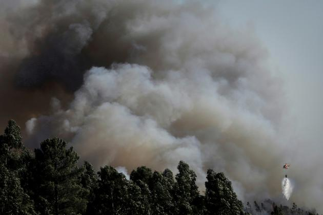 Un hélicoptère largue de l'eau sur un incendie qui fait rage près de Monchique dans la région de l'Algarve au Portugal, le 8 août 2018 [CARLOS COSTA / AFP]