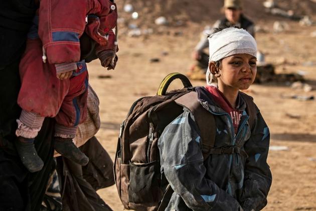 Un enfant, la tête enroulée dans un bandage, patiente dans un point de rassemblement contrôlé par les Forces démocratiques syriennes, après avoir quitté le dernier réduit du groupe Etat islamique, le 5 mars 2019 [Delil SOULEIMAN / AFP]