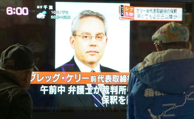 Des piétons passent devant un écran de télévision sur lequel apparaît le visage de de Greg Kelly, ancien bras droit de Carlos Ghosn, le 21 décembre 2018 à Tokyo, au Japon [Kazuhiro NOGI / AFP/Archives]