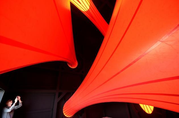 """Un visiteur photographie une oeuvre du sculpteur britannique Anish Kapoor lors de l'ouverture de l'exposition """"Anish Kapoor: œuvres, pensées, expériences"""", le 6 juillet 2018 dans le parc de la Fondation Serralves, à Port, au Portugal [MIGUEL RIOPA / AFP]"""