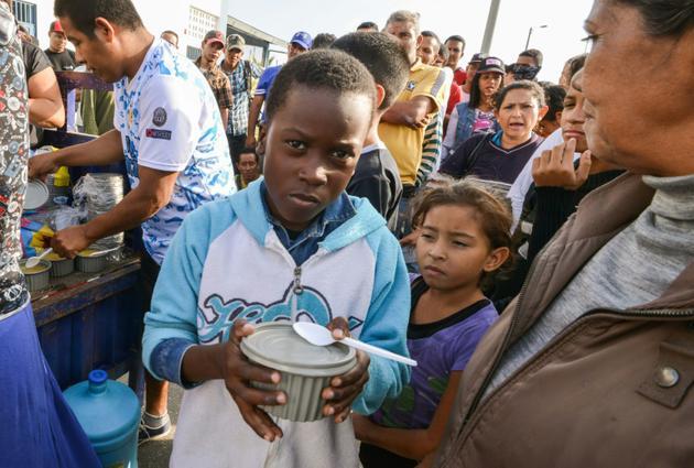 Des migrants vénézuéliens qui ont fui la crise économique dans leur pays reçoivent de l'aide et de la nourriture à Tumbes, au Pérou, à la frontière avec l'Equateur, le 23 août 2018 [CRIS BOURONCLE / AFP]