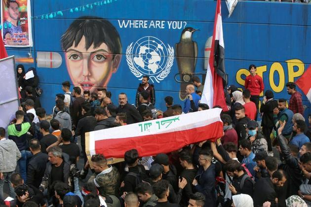 Des Irakiens portent le cercueil d'un jeune manifestant tué la veille, le 1er décembre 2019 sur la place Tahrir, dans le centre de Bagdad [SABAH ARAR / AFP]