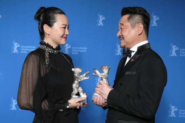 """Les acteurs chinois Wang Jingchun et Yong Mei posent avec leur Ours d'argent de meilleurs acteurs pour le film """"So Long, My Son"""" lors de la cérémonie de la 69e Berlinale le 16 février 2019 à Berlin. [Christoph SOEDER / POOL/AFP]"""