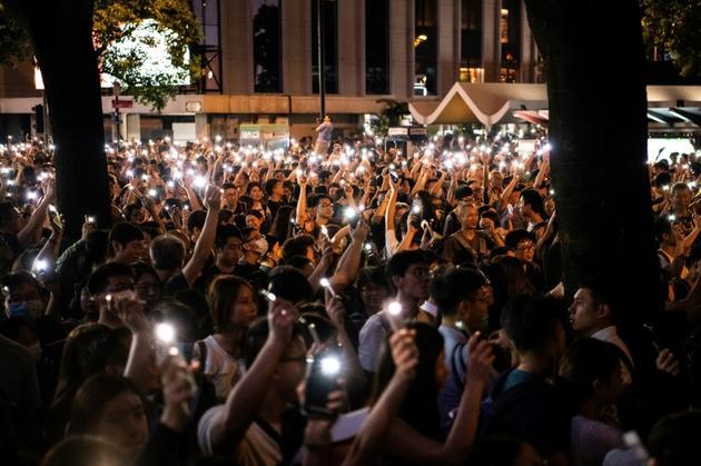 Des protestataires brandissent la lumière de leur téléphone portable lors d'une manifestation de fonctionnaires dans le centre-ville de Hong Kong, le 2 août 2019 [Laurel Chor / AFP]