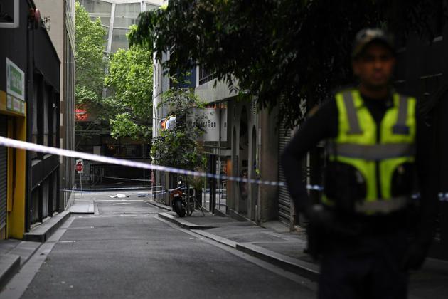 Un corps est allongé sur la chaussée tandis qu'un policier monte la garde après une attaque au couteau le 9 novembre 2018 à Melbourne.<br /> [WILLIAM WEST / AFP]