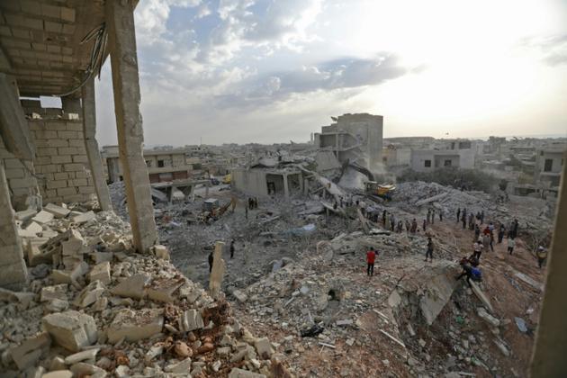 Des civils se rassemblent au milieu des destructions à Zardana, dans le nord de la province d'Idleb en Syrie, après des raids aériens du régime ou de l'allié russe le 8 juin 2018 [OMAR HAJ KADOUR / AFP/Archives]