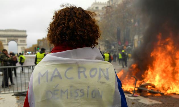 """""""Macron démission"""" peut-on lire sur ce gilet jaune, sur les Champs Elysées, le 24 novembre 2018 [Bertrand GUAY / AFP]"""