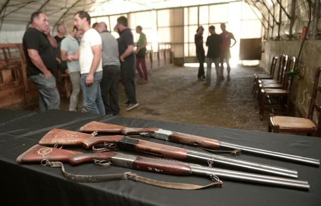 Des agriculteurs discutent le 20 septembre, les fusils sur une table, alors que se tient une réunion sur la réintroduction de deux ourse dans les Pyrénées occidentales [IROZ GAIZKA / AFP]