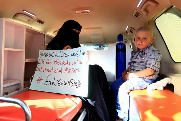 Une Yéménite, assise près de son fils malade dans une ambulance, tient une pancarte appelant à lever le blocus à l'aéroport de Sanaa, en attendant l'arrivée de l'émissaire de l'ONU Martin Griffiths, le 5 janvier 2019 [Mohammed HUWAIS / AFP]
