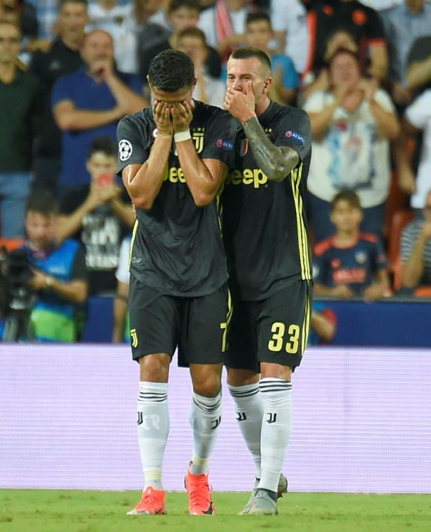 L'attaquant de la Juventus Cristiano Ronaldo (g) anéanti après son exclusion face à Valence en 1re journée de Ligue des champions le 19 septembre 2018 [JOSE JORDAN / AFP]