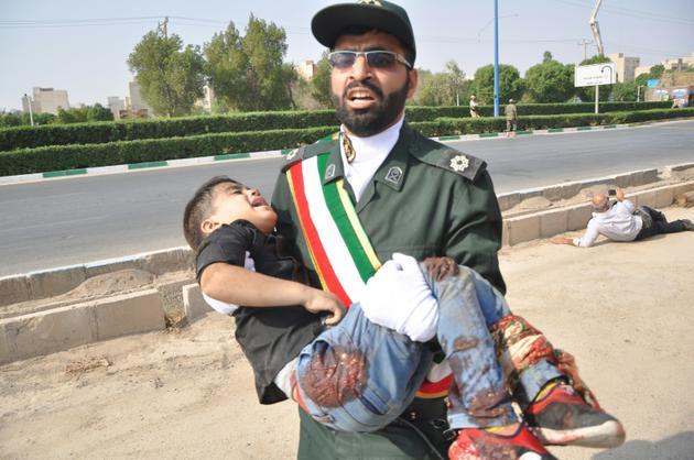 Un Gardien de la révolution porte un enfant blessé lors d'une attaque à Ahvaz, dans le sud-ouest de l'Iran, le 22 septembre 2018 [Shayan HAJI NAJAF / ISNA/AFP]