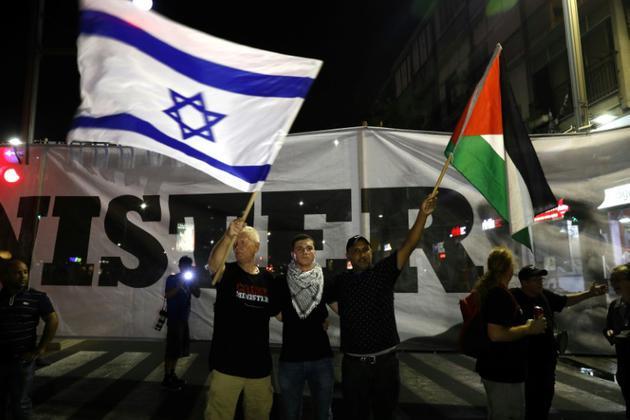 """Des drapeaux israélien et palestinien brandis lors d'une manifestation d'Arabes israéliens contre une loi définissant Israël comme """"l'Etat-nation du peuple juif"""", le 11 août 2018 à Tel-Aviv [Ahmad GHARABLI / AFP]"""