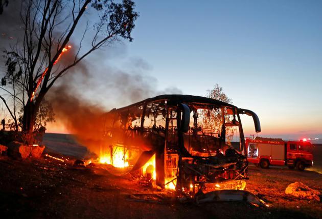 Un bus en feu le 12 novembre 2018 en Israël, à proximité de la bande de Gaza, après avoir été touché par une roquette tirée de l'enclave palestinienne [Menahem KAHANA / AFP]
