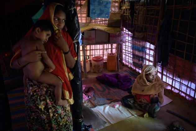 Setara, 20 ans (d), sa fille juste née dans ses bras, tandis qu'une amie (g) tient un autre de ses enfants, le 9 août 2018 dans le camp de réfugiés rohingyas de Thangkhali près de Cox's Bazar [Ed JONES / AFP/Archives]