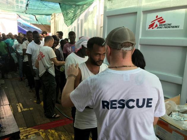 Un membre de l'équipe de sauvetage de l'Ocean Viking parle avec un migrant à bord du navire humanitaire, le 21 août 2019 [Anne CHAON / AFP/Archives]