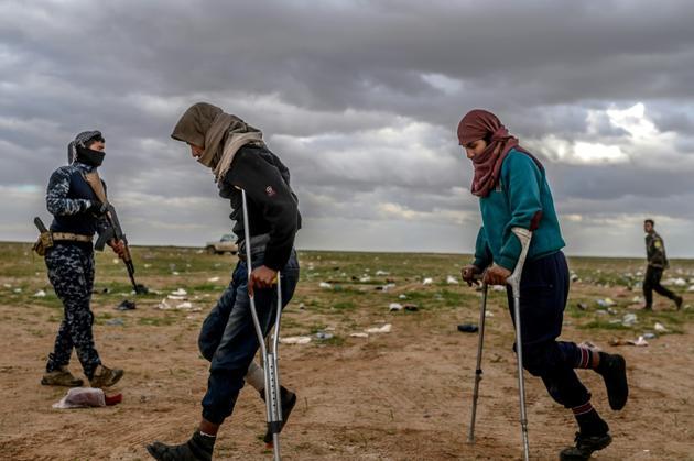 Des hommes soupçonnés d'être des membres du groupe Etat islamique attendent d'être fouillés par les combattants des Forces démocratiques syriennes, après avoir quitté le dernier réduit de l'EI à Baghouz, dans l'est syrien, le 27 février 2019 [Bulent KILIC / AFP]