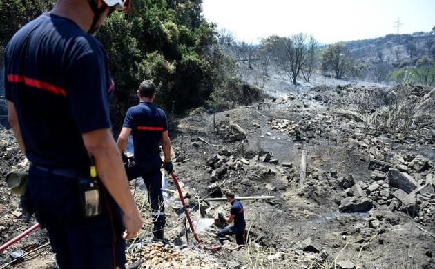 Des pompiers en intervention après un feu de végétation dans le Gard, à Saint-Gilles le 29 juin 2019</p> <p> [SYLVAIN THOMAS / AFP]