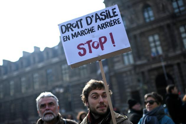 """Un homme brandit une pancarte """"Droit d'asile en marche arrière - Stop"""" dans une manifestation organisée par l'OFPRA contre la loi asile et immigration, le 21 février 2018 à Paris<br />  [STEPHANE DE SAKUTIN / AFP/Archives]"""