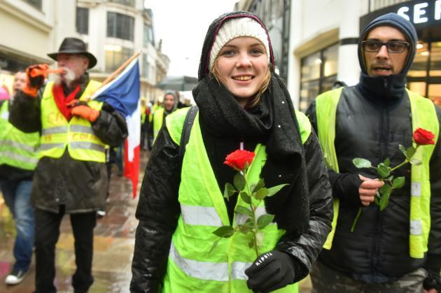 """Des """"gilets jaunes"""" avec une rose, en hommage aux victimes de Strasbourg, défilent le 15 décembre 2018 au Mans [JEAN-FRANCOIS MONIER              / AFP]"""