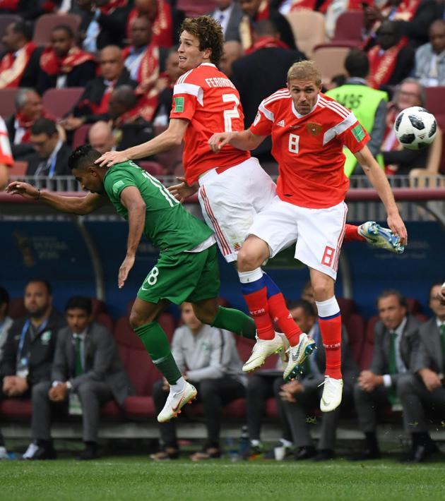 L'attaquant saoudien Salem Al-Dawsari (g) à la lutte avec les Russes Mario Fernandes (c) et Yuri Gazinskiy lors du match d'ouverture du Mondial, le 14 juin 2018 à Moscou    [Kirill KUDRYAVTSEV / AFP]