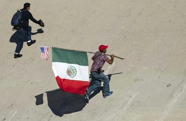 Un migrant portant les drapeaux mexicain et étatsunien tente de passer la frontière entre le Mexique et les Etats-Unis le 25 novembre 2018 à Tijuana [Pedro PARDO / AFP]