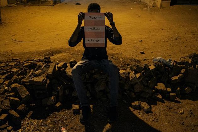 Le manifestant soudanais Mustafa dissimule son visage derrière une affiche réclamant