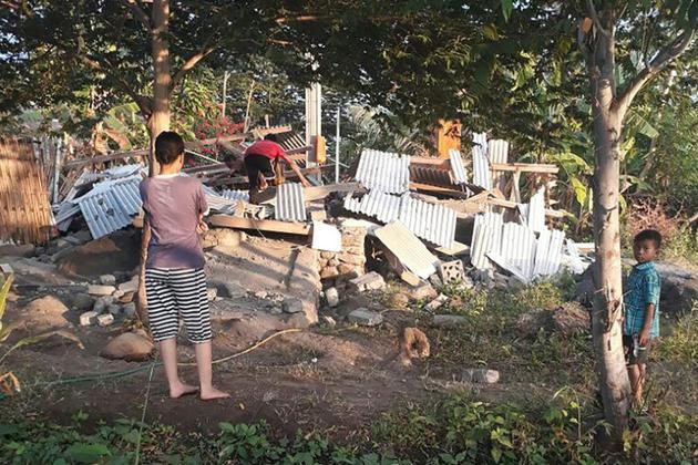 Des Indonésiens parmi les décombres de maisons à Lombok, en Indonésie, après un séisme de magnitude 6.4, le 29 juillet 2018 (photo transmise par l'agence de gestion des catastrophes indonésienne) [Handout / Nusa Tenggara Barat Disaster Mitigation Agency/AFP]