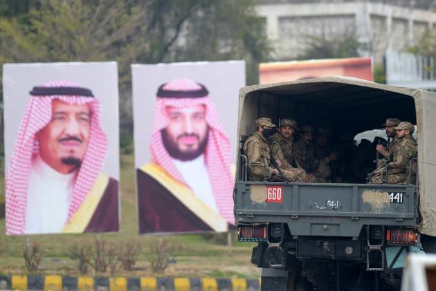 Des soldats pakistanais patrouillent dans les rues d'Islamabad à côté d'affiches accueillant le prince héritier saoudien Mohammed ben Salmane, le 17 février 2019  [AAMIR QURESHI / AFP]