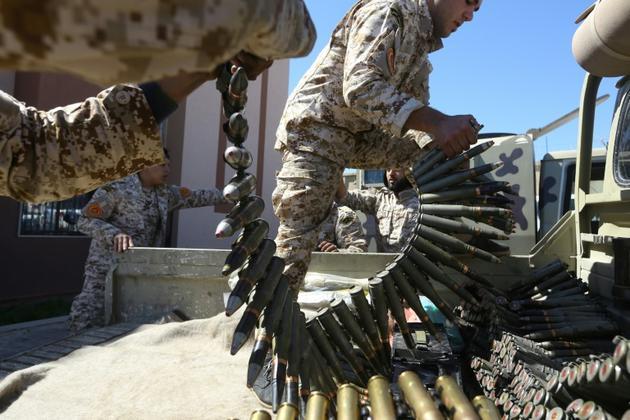Des combattants loyaux au Gouvernement d'union nationale préparent leurs armes contre les focres de Khalifa Haftar, le 8 avril 2019 près de Tripoli. [Mahmud TURKIA / AFP]