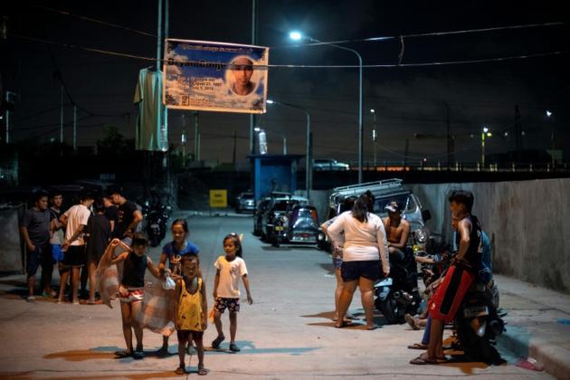 Des Philippins sous le portrait à la mémoire de Bryan Conje, retrouvé mort le 5 juillet sous le pont où il vivait, le 7 juillet 2019 à Manille [Noel CELIS / AFP]