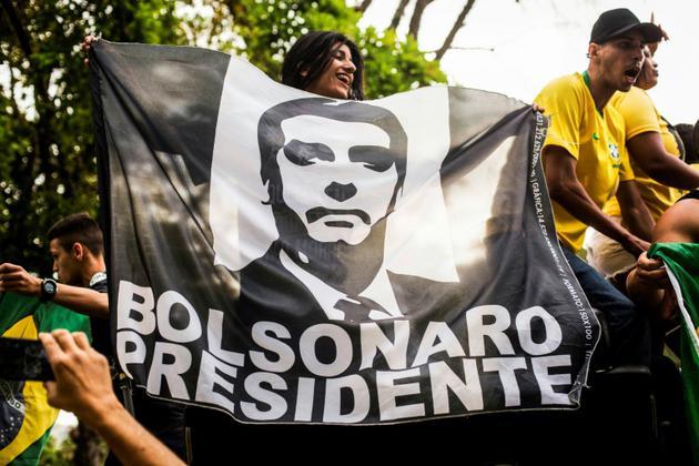 Des soutiens de Jair Bolsonaro défilent avec une affiche représentant leur candidat pour l'élection présidentielle brésilienne, le 29 septembre 2018 à Rio de Janeiro [DANIEL RAMALHO / AFP/Archives]