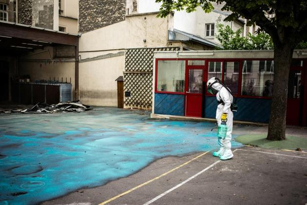 Un employé pulvérise un gel sur le sol de la cour de l'école Saint-Benoît, près de Notre-Dame de Paris, pour réduire les risques de contamination au plomb, le 8 août 2019  [Martin BUREAU / AFP/Archives]