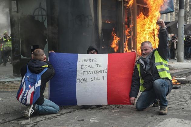 """Des """"gilets jaunes"""" brandissent un drapeau français sur lequel est écrit """"liberté, égalité, fraternité, mon cul!"""" alors qu'un kiosque à journaux flamble sur les Champs-Elysées à Paris le 16 mars 2019  [Zakaria ABDELKAFI / AFP/Archives]"""