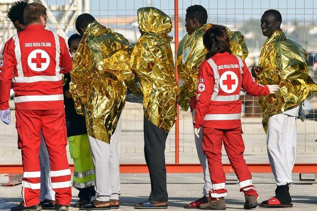 Des membres de la Croix-Rouge italienne prennent en charge des migrants débarqués du bateau de l'ONG allemande Sea Watch3, le 8 novembre 2017 à Pozzallo, en Sicile [Giovanni Isolino / AFP/Archives]