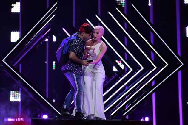 Un spectateur s'empare du micro de la Britannique Susanna Marie Cork alias SuRie avant d'être interpellé pendant la finale de la 63e édition du concours de l'Eurovision, à Lisbonne le 12 mai 2018 [Francisco LEONG / AFP]
