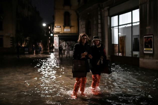 Des badauds, chaussés de sacs en plastique, à Venise le 12 novembre 2019<br />  [Marco Bertorello / AFP]